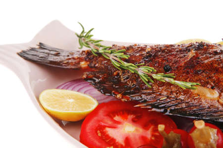 savory: whole fryed sunfish over plate with tomatoes lemons and peppers photo
