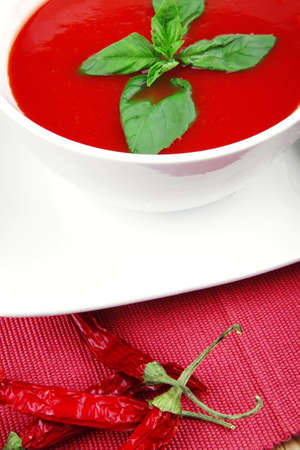 diet food : hot tomato soup with basil thyme and dry pepper in big bowl over red mat on wood table ready to eat photo