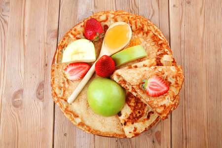 dessert : thin round pancake with honey strawberries and apple on wooden table Stock Photo - 13519585