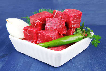 raw fresh beef meat slices in a white bowls with dill and green hot peppers serving over blue wooden table photo