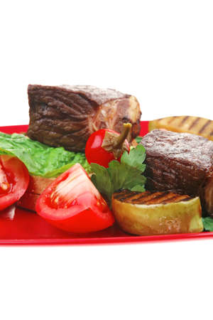 bbq : beef (pork) steak garnished with apples , fresh tomatoes, hot pepper, chives and lettuce, on bread, over red plate isolated on white background Stock Photo - 13519405