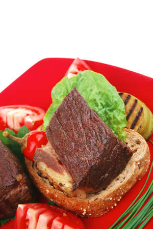 meat savory : beef roasted and garnished with baked apples, raw tomatoes, green chives and pepper, over bread slice on red plate isolated over white background photo