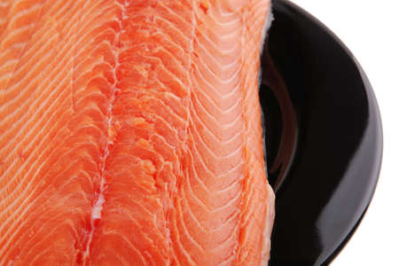 fresh raw salmon fillet on black over white photo