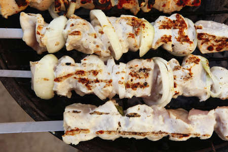 grilled and raw chicken shish kebab cooked on barbecue appliance photo