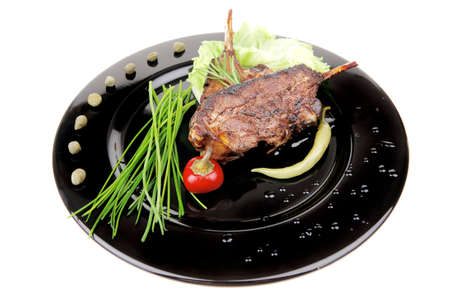 savory plate: grilled ribs over black with peppers and green salad photo