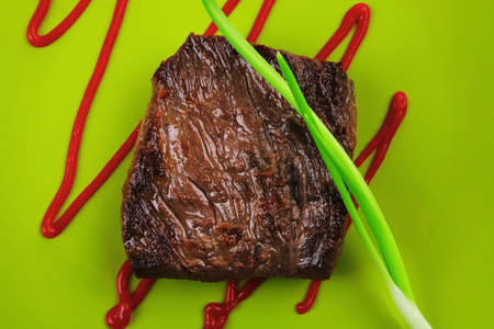 meat food : roast beef fillet mignon served on green plate with chives and ketchup isolated over white background photo
