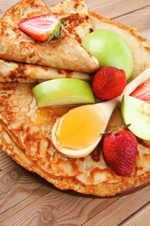 baked food : pancake with honey strawberries and apple on wooden table photo