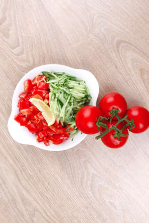 whole tomatoes on branch with salad of shredded tomatoes and cucumbers on white dish over wood table Stock Photo - 13633508