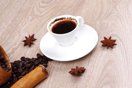 sweet hot drink : black Turkish coffee in small white mug with mortar and pestle , coffee beans over a wooden table , decorated with cinnamon sticks and anise stars Stock Photo - 13633572