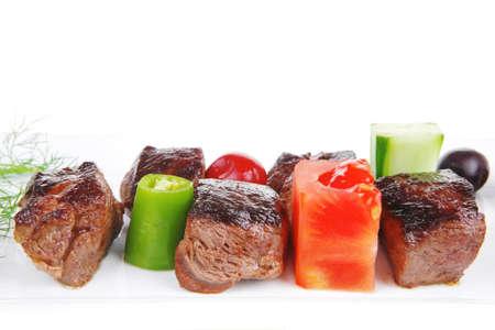 european food: comida europea: carne asada carne de estofado sobre plato blanco sobre fondo blanco con verduras