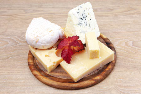 various types of cheese on wooden platter over wooden table photo