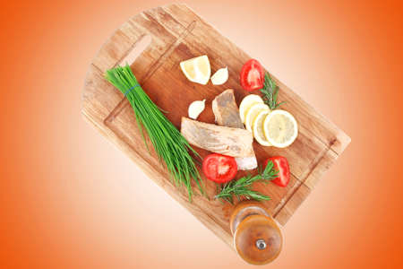 savory sea fish entree : roasted salmon fillet with green onion, red cherry tomatoes pieces, glass pepper grinder, rosemary twigs and lemon on wooden board isolated on white background photo