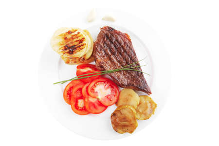 meat food : roast beef fillet steak served on white plate with tomatoes , potatoes , and chives isolated over white background photo