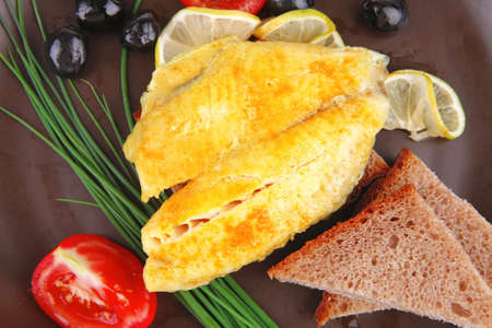 roast fish fillet with tomatoes,chives and bread on plate photo