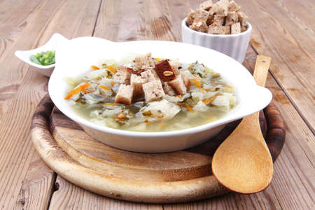 hot fresh diet vegetable soup with rye bread crackers over wood table on stand photo