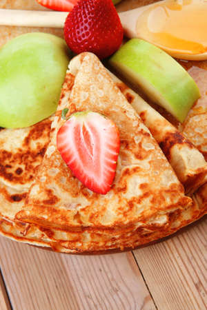 baked and fruits : pancake with honey strawberries and apple on wooden table photo