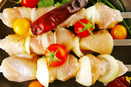 raw chicken kebabs served on skewers with vegetables photo