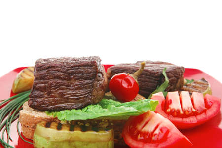 barbecued meat : beef ( lamb ) garnished with baked apples , fresh raw tomatoes, hot pepper, on bread, over red plate isolated on white background Stock Photo - 13809082