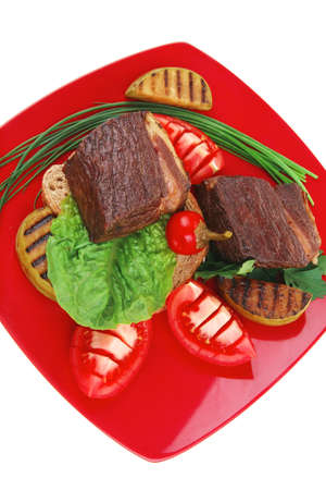 meat food : grilled beef garnished with apples and fresh raw tomatoes with hot pepper over bread slice on red plate isolated over white background Stock Photo - 13809231