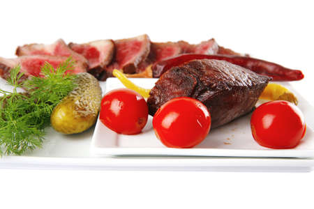 meat sliced with tomatoes and peppers on white photo