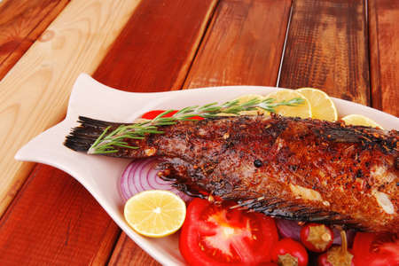 fryed: savory: whole fryed sunfish over wood with tomatoes lemons and peppers Editorial