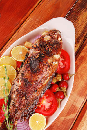 main course: whole fried seabass served on wood with lemons,tomatoes and peppers Stock Photo - 14135535