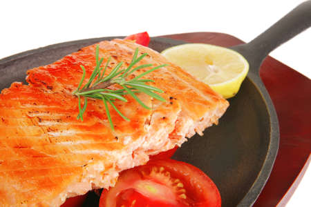 food: hot grilled salmon on metal pan over wooden plate isolated on white background