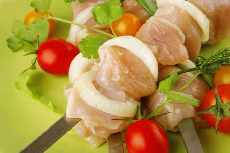 served raw chicken kebabs on dark plate