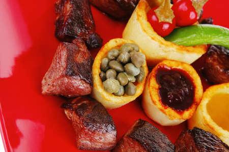 european food: comida europea: carne asada carne de estofado sobre la placa de color rojo sobre fondo blanco con tomate y eneldo y salsa de barbacoa Editorial
