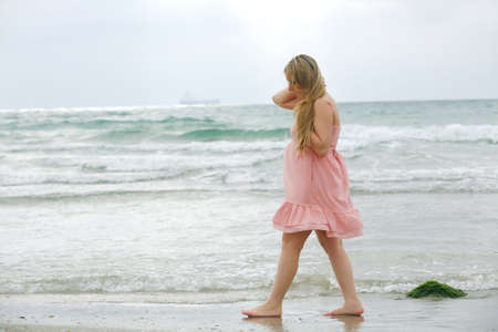 Portrait of beauty young woman in pink dress posing at a beach on sea background photo