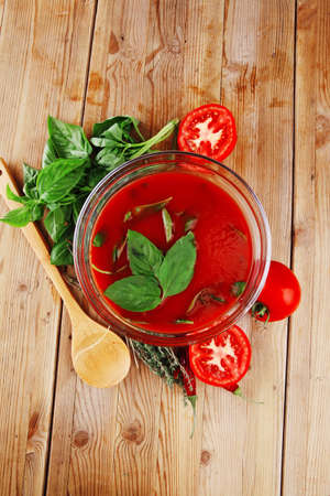 cold fresh diet tomato soup with basil thyme and raw tomatoes in transparent bowl over red mat on wood table ready to eat