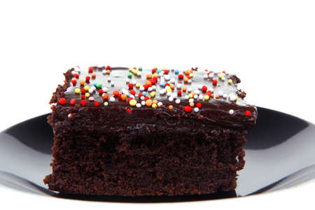 sweet food : black chocolate cake on saucer isolated over white background
