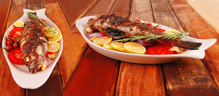 savory: whole fryed sunfish over wood with tomatoes lemons and peppers Stock Photo - 13978648