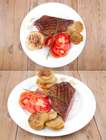 meat food : roasted fillet mignon on white plate with tomatoes and chives served on wooden table photo