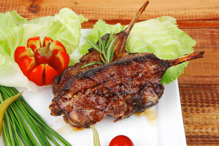 meat savory on wooden table: roast ribs on white plate with peppers lettuce tomato and chives photo