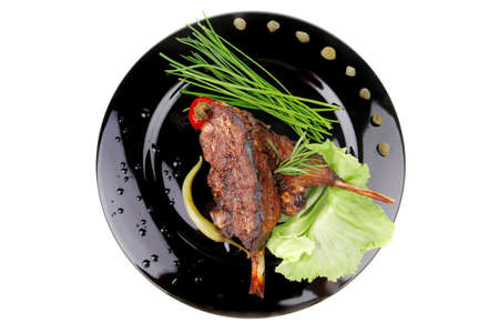 served savory plate: meat ribs with chives and red hot peppers photo