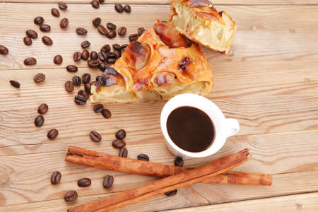 sweet round apple pie on wooden table with coffee cup and cinnamon sticks photo