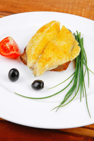main portion: served roast golden fish fillet over white plate on wooden table with tomatoes and olives Stock Photo - 14158542