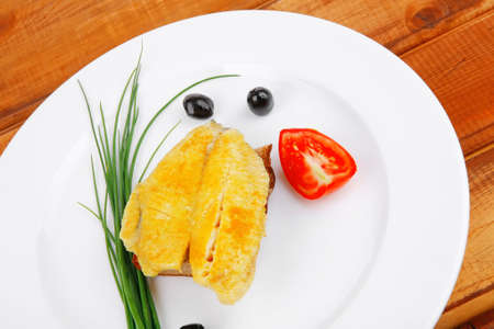 main portion: served roast golden fish fillet over white plate on wooden table with tomatoes and olives Stock Photo - 14158795