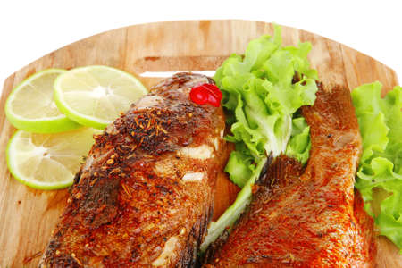 roast golden fish on wooden plate served with lemon and salad photo