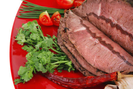 beef slice on red plate and vegetables photo