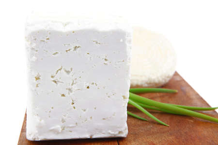 diet food : greek feta white cheese served on small wooden plate isolated over white background photo