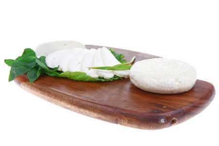 mediterranean cuisine : raw soft feta white cheese round with slices on wooden plate isolated over white background Stock Photo - 14270709