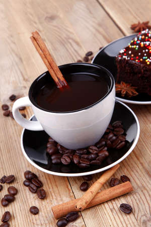 spice cake: sweet dessert : black coffee and chocolate cake with cinnamon , coffee beans, and anise star on wooden table