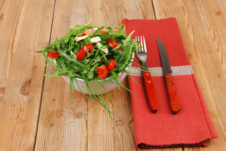 vegetable salad : green salad with raw tomato and garlic in white bowl over wood served with cutlery photo