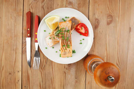 savory fish portion : grilled norwegian salmon fillet with green chinese onion, red cherry tomatoes , allspice pepper in grinder, rosemary twigs and lemon slice on wooden board photo