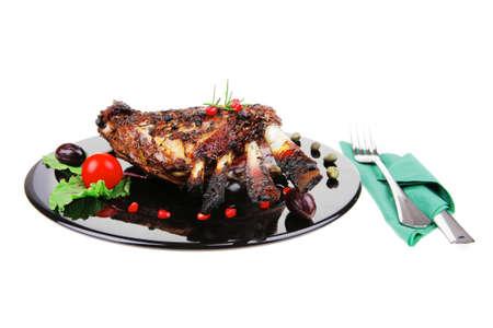 baby cutlery: costillas asadas del beb� en plato negro con cubiertos Foto de archivo