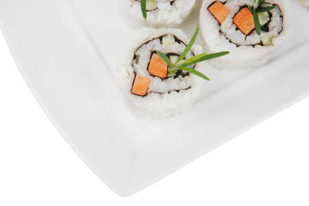 Japanese Cuisine - California Roll made of Fresh raw Salmon, Cream Cheese and Avocado inside. Served with wasabi and ginger . on long white plate isolated over white background photo