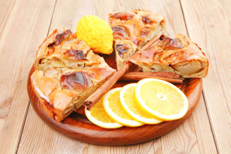 baked food : apple pies on wooden plate over table with cinnamon sticks and lemons photo