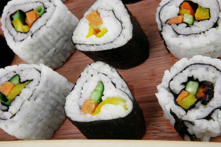 Japanese Cuisine - Maki Roll with Deep Fried Vegetables inside . on wooden plate . isolated over white background photo